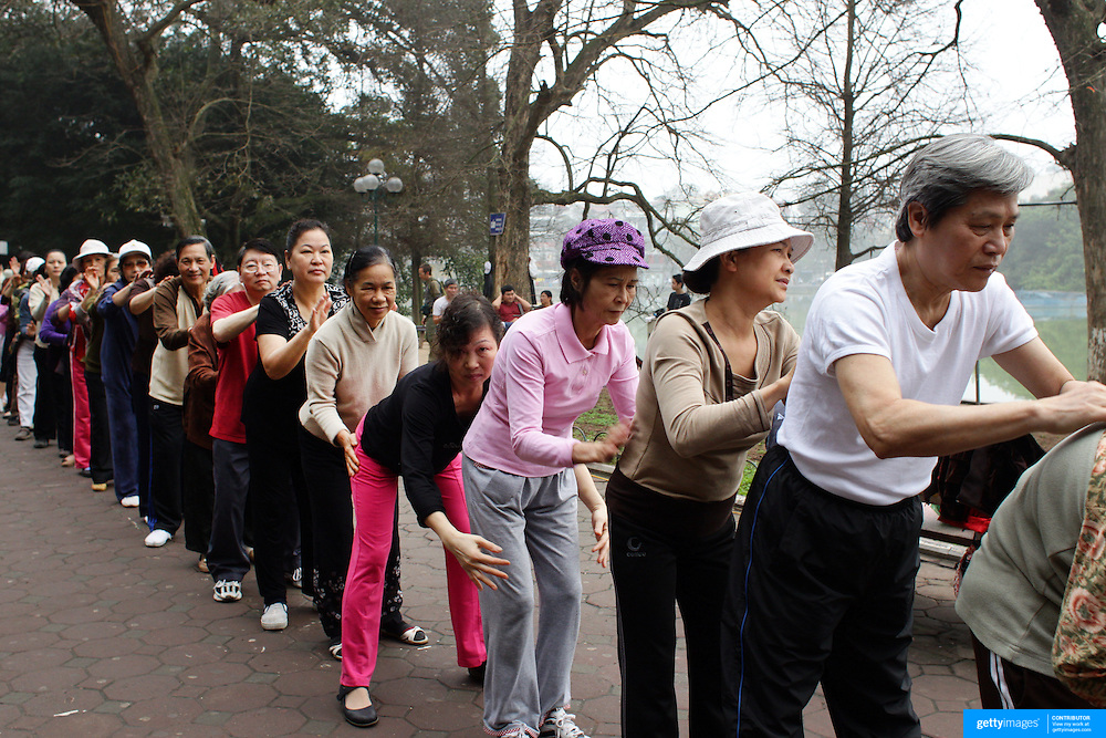 An elderly keep fit class massage each other in a group fitness session besides Hoan Kiem Lake, Hanoi, Vietnam.. For a county not know for it's sporting prowess, Hanoi, Vietnam's capital, appears to be gripped in a fitness frenzy. Before 6am street corners, parks and lake sides are a hive of activity as keep fit classes, Tai chi and personal exercise regimes are seen in abundance around the city. Particularly noticeable are Women's keep fit classes, often accompanied by loud poor quality western disco beat music as the occupants of the city get fit come rain or shine. Hanoi, Vietnam. 18th March 2012. Photo Tim Clayton