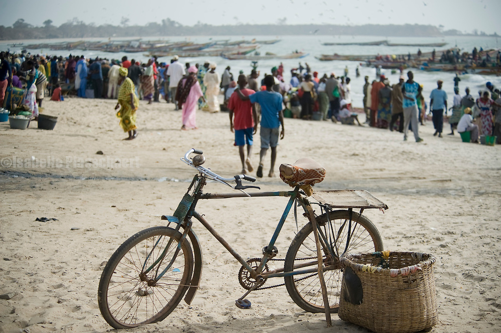 Fishermen coming in at Tanji, people selling and buying fish.