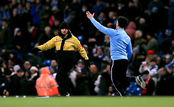 A pitch invader runs across the pitch at the end of the match