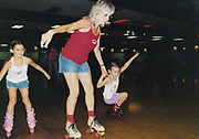 A mother and her daughters rollerblading, USA