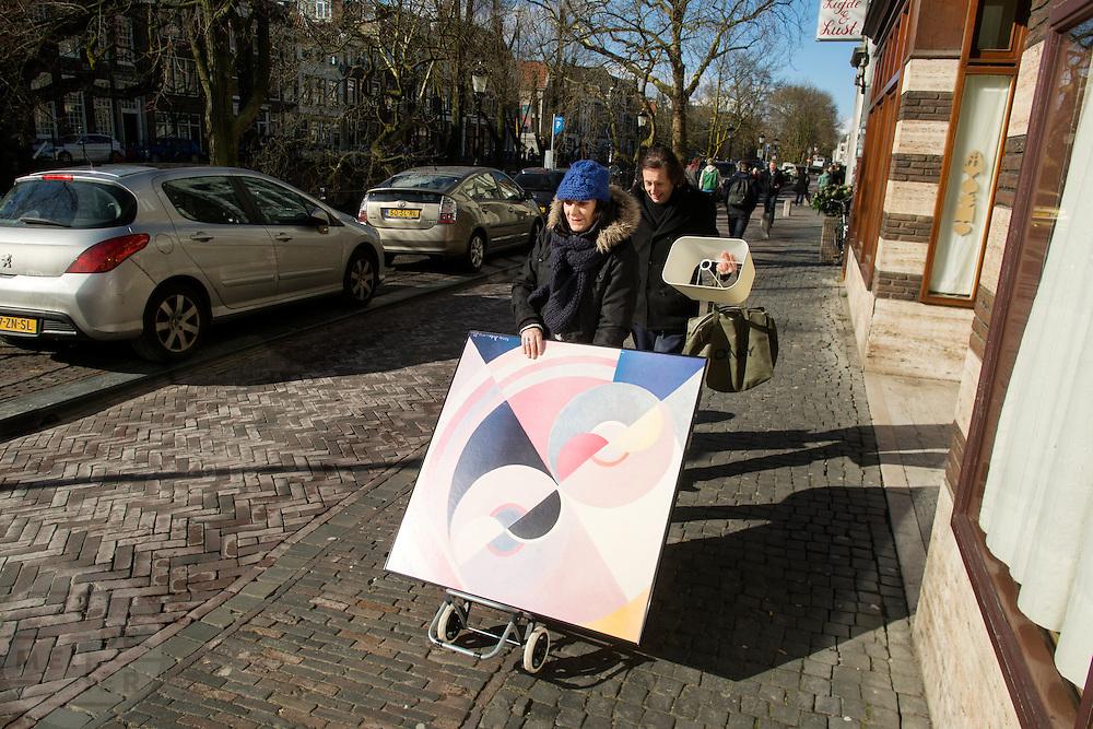 Een man en vrouw lopen met een schilderij langs de Oudegracht in Utrecht.<br /> <br /> A man and woman are walking with a painting at the Oudegracht in Utrecht.