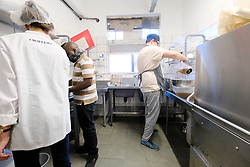 JOHANNESBURG SOUTH AFRICA - MAY 01 Croft & Co staff and owners prepare meals for delivery on May 01, 2020 in Johannesburg South Africa. South Africa moved down to Level 4 of the national lockdown with relaxed restrictions as part of a risk adjusted 5 stage phasing of lockdown measures. This includes allowing of certain restaurants to reopen for trade and prepare hot food as delivered takeaway only. (Photo by Gallo Images/ Dino Lloyd)