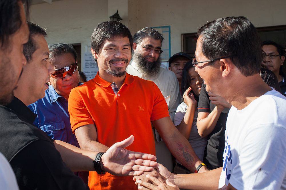 Manny Pacquiao shakes the hand of Jimmy Sambo Yaokasin, Vice Mayor of Tacloban City during his visit. <br /> <br /> Manny Pacquaio visits victims of Typhoon Yolanda in Tacloban City.  Leyte, Philippines  December 2, 2013