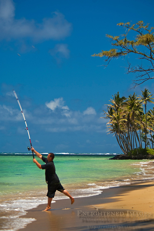 Fisherman casting from the shore at Punalu'u Beach Park, Oahu, Hawaii