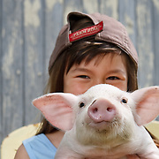 Smiling girl 8-10 years holds up piglet to camera looking at camera horizontal