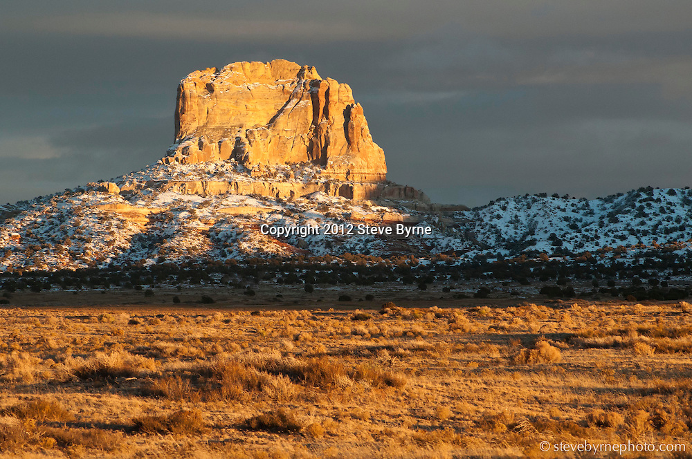 Winter afternoon light ignites a tombstone coated in fresh snow near Page, Arizona.