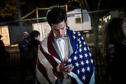 A man, draped in the United States Flag, somberly watches as election results come in while he stands in front of the White House in Washington early on the morning of Nov. 9, 2016. After a long and bitter campaign, President-Elect Donald J. Trump, republican nominee, was elected to be the 45th president.