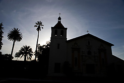 Silhouette of Mission Santa Clara de Asís, Mission Church, at sunset with palm trees, Santa Clara University, Santa Clara, California, United States of America.