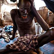 Camp Ifo III. Issac Ali Hassan, 60 ans, de Salaghaley. Il a été victime de tuberculose quelques années plus tôt. Aujourd'hui, il présente vraisemblablement des symptômes de pneumonie et commence à s'inquiéter de son état. Il se repose dans sa tente. MSF a installé des cliniques de proximité dans les camps. Mais Issac est trop faible pour se déplacer. Ce jour-là, il rencontre un médecin de MSF dépêché sur le terrain, de quoi le rassurer et l'aiguiller sur le traitement à prendre.