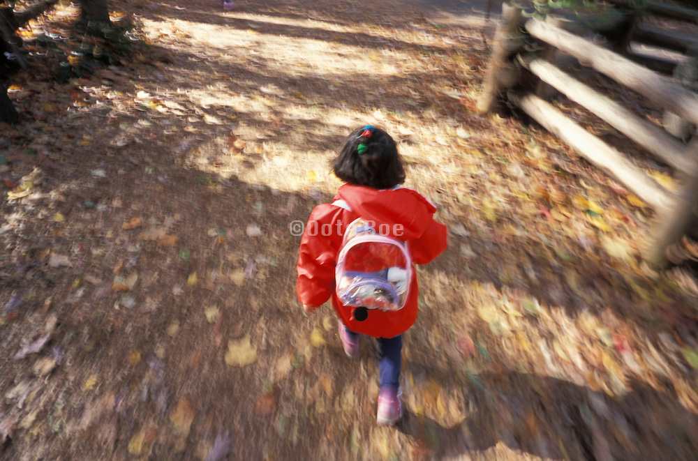 young girl running wearing backpack