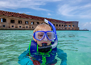 Child snorkeling at Dry Tortugas National Park. The boy wears a blue snorkel, goggles, and rash guard, emerging from the beautiful clear and turquoise water outside of historic Fort Jefferson. Model released photo.