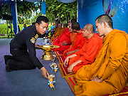 11 AUGUST 2015 - BANGKOK, THAILAND:       An employee of the Bangkok Metropolitan Authority makes an offering to Buddhist monks during a service to honor Queen Sirikit of Thailand before her 83rd birthday. Queen Sirikit was born Mom Rajawongse Sirikit Kitiyakara on August 12, 1932. She is the queen consort of Bhumibol Adulyadej, King (Rama IX) of Thailand. She met Bhumibol in Paris, where her father was the Thai ambassador. They married in 1950, she was appointed Queen Regent in 1956. The King and Queen had one son and three daughters. She has not made any public appearances since her hospitalization in 2012. Her birthday is celebrated as Mother's Day in Thailand, schools and temples across Thailand hold ceremonies to honor the Queen and mothers.    PHOTO BY JACK KURTZ