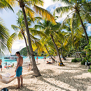 Hammocks are strung between the palm trees on the sandy beach in front of the Soggy Dollar Bar at White Bay on Jost Van Dyke in the British Virgin Islands.