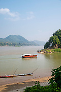 A boat plies the waters of the Mekong River and enters the Nam Khan River, Luang Prabang, Laos.
