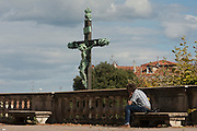 A crucified Christ on the cross with local man in Place du Peyrou, Montpellier, south of France.