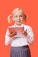 Portrait of a happy young schoolgirl holding tablet PC over orange background