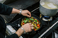 "NAPLES, ITALY - 10 OCTOBER 2018: Chef Potito Izzo prepares the ""melanzane a funghetto"", a side dish made of egglplants and Vesuvian cherry tomatoes, at La Taverna a Santa Chiara, in the historical center of Naples, Italy, on October 10th 2018.<br /> <br /> The idea of the founders Nives Monda and Potito Izzo (two really unusual names in southern Italy) was to create a ""taste gate"" of Campania products. La Taverna a Santa Chiara, founded in 2013, is a modern tavern whose strengths are the choice of regional and seasonal products and mostly small producers. Small restaurant, small producers.<br /> The two partners tried to put producers and consumers in direct contact, skipping the distribution, and managing to reduce the costs of the products considerably. Nives and Potito managed to create a simple kitchen, at moderate costs but with high quality raw materials.<br /> ""A different restaurant idea,"" says Nives, ""the producers deliver their products at low prices and the tavern manages to make traditional dishes with niche products"".<br /> Nives Monda has been a labor consultant for 20 years. Potito Izzo is the chef who has always been loyal to the  family cuisine. When he embraced the idea of Nives he found in the tavern the natural place to express the tradition of Neapolitan cuisine. Nives defines him as a ""comfort food chef"". Their partnership is a true friendship that has lasted for over 10 years."