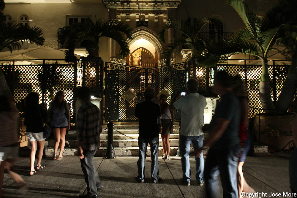 People gather outside the former residence of designer Gianni Versace on South Beach. The mansion is now The Villa by Barton G., a hotel and restaurant. The Mansion is now  The eclectic South Beach neighborhood of Miami Beach glitters with nightlife – all day long along its Art Deco hotels. People watching is a great pastime in this trendy and quirky area which draws celebrities and beautiful people from all over the world. Enjoy the beach or the historic Art Deco architecture or the fine Oceanside dining. <br /> <br /> Photography by Jose More