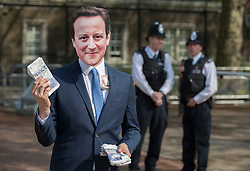 © Licensed to London News Pictures. 12/05/2016. London, UK. Police look on as a protestor dressed as Prime Minister David Cameron offers fake money as he stands outside the anti-corruption summit. The real Mr Cameron is hosting a one day summit which is addressing world corruption. Photo credit: Peter Macdiarmid/LNP