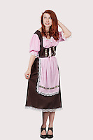 Young confused woman in maid costume standing against gray background
