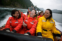 The exhilaration of running swift flowing water near Hole in the wall at Sonora Island is captured on the faces of these passengers as giant whirlpools and racing water flows swiftly beneath the hull of their Zodiak.  Sonora Island, Discovery Islands,   British Columbia, Canada.