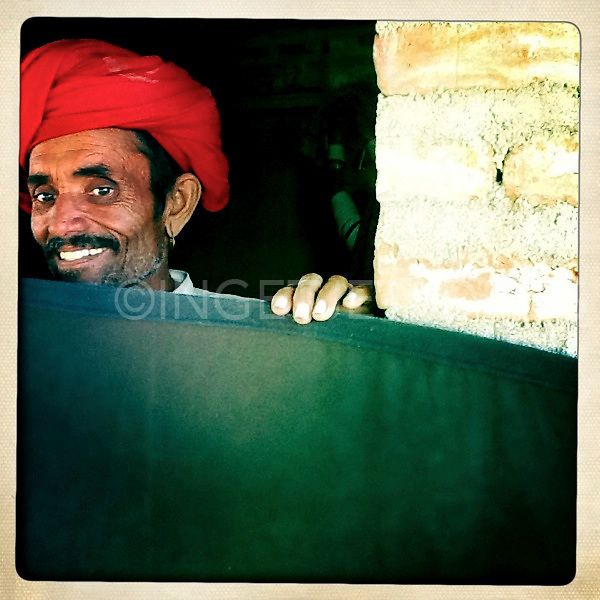 Rabari man peeking over a backdrop