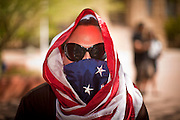 """22 OCTOBER 2011 - PHOENIX, AZ:    An Occupy Phoenix with his head wrapped in an American flag at Cesar Chavez Plaza in downtown Saturday. The demonstrations at Occupy Phoenix, AZ, entered their second week Saturday. About 50 people are staying in Cesar Chavez Plaza, in the heart of downtown. The crowd grows in the evening and on weekends. Protesters have coordinated their actions with police and have gotten permission from the city to set up shade shelters and sleep in the park, but without tents or sleeping bags, which is considered """"urban camping,"""" instead protesters are sleeping on the sidewalk. PHOTO BY JACK KURTZ"""