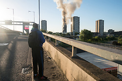 © Licensed to London News Pictures. 14/06/2017. London, UK. Photo credit: A young man watches a major fire that has engulfed the 27-storey Grenfell Tower block in Latimer Road, White City. The blaze started early Wednesday morning and has spread through most of the building. Ray Tang/LNP
