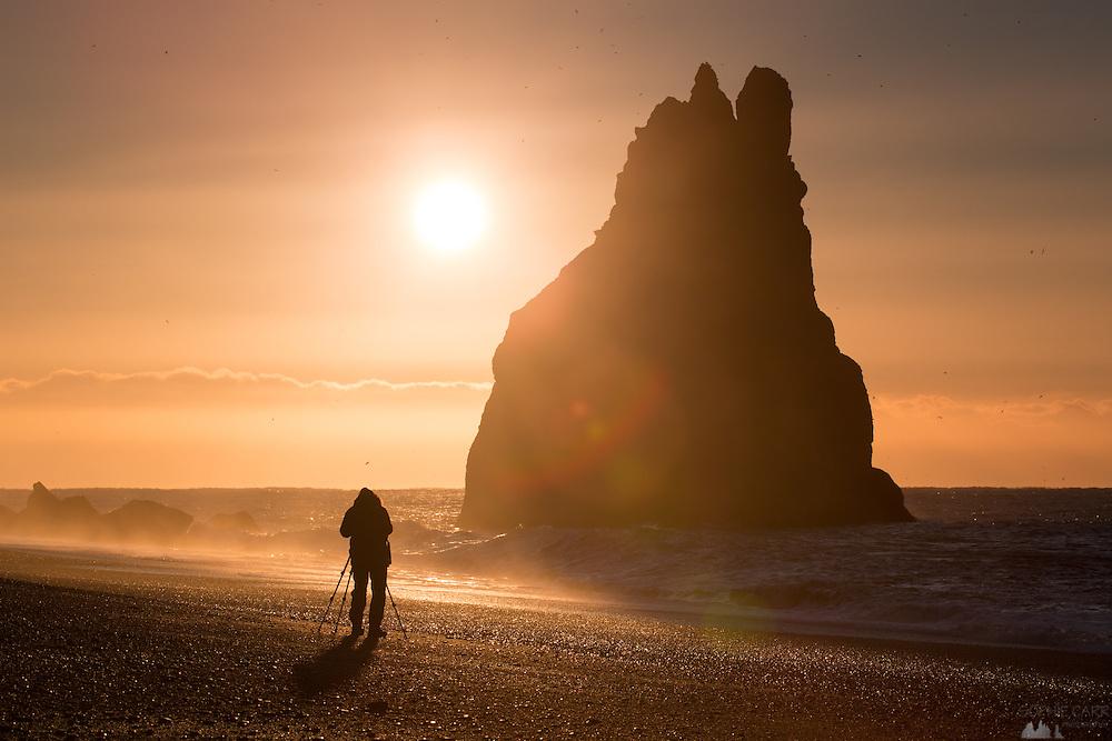 A photographer on the beach at Reynisfjara, near Vik, at sunrise