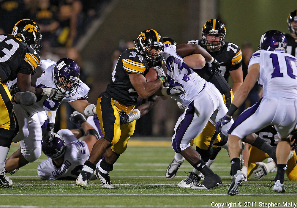 October 15, 2011: Iowa Hawkeyes running back Marcus Coker (34) tries to break a tackle by Northwestern Wildcats linebacker David Nwabuisi (33) during the first half of the NCAA football game between the Northwestern Wildcats and the Iowa Hawkeyes at Kinnick Stadium in Iowa City, Iowa on Saturday, October 15, 2011. Iowa defeated Northwestern 41-31.