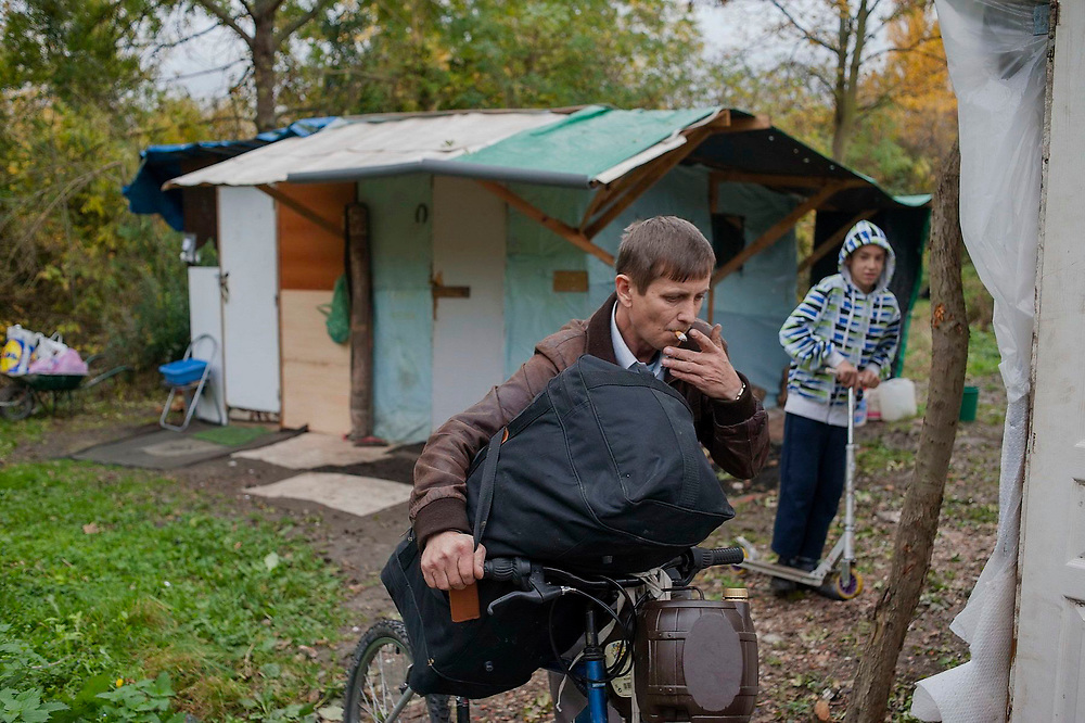A man pushing a bicycle with a large bag smokes a cigarette while walking across a settlement of makeshift shelters which has been built by a group of around 80 people from Calinesti Oas who have built huts out of materials they have been able to find.Many have been living here since 2002. Some of them have not found work in France and therefore can't afford to pay rent. Others prefer to live in these makeshift settlements to save money. Ion is planning to return to Romania since he wasn't able to find any work.