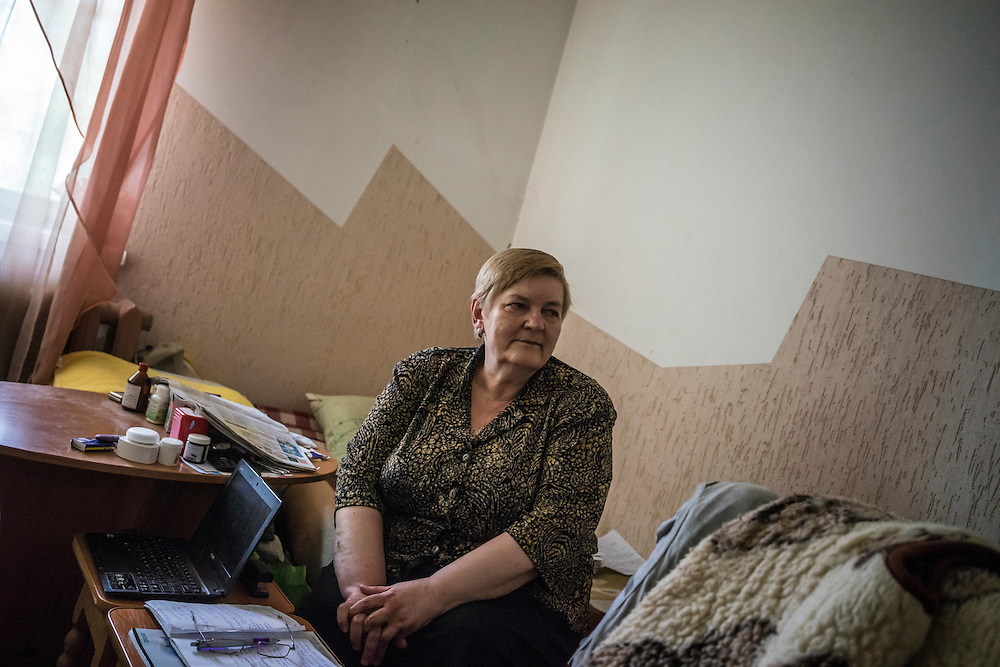 Ewa Holodkova, 67, from the town of Stakhanov in Lugansk oblast, poses for a portrait in the room where she lives with her husband on Tuesday, April 28, 2015 in Lviv, Ukraine. Despite being a Polish citizen and she and her husband having the legal right to live in Poland, where they have a daughter, their Ukrainian pensions are too small to afford life in Poland. CREDIT: Brendan Hoffman/Prime for the Wall Street Journal UKRMIGRATION