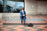 © Licensed to London News Pictures. 28/09/2014. Birmingham, UK. A delegate sits outside the conference centre. The Conservative Party Conference in Birmingham 28th September 2014. Photo credit : Stephen Simpson/LNP