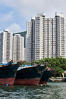 Fishing boats moored in Aberdeen fishing village with high rise apartment blocks behind Hong Kong Hong Kong August 2008