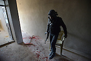 "Aleppo, Syria, December, 2012 - An FSA rebel tries to avoid stepping in the blood of a fallen comrade. The rebel is from ""Battallion 80,"" which organized an operation to take the city's airport where more then 1500 men from the Syrian Army are holed up with more than 20 Mig Jets and 40 helicopters.  The FSA lost 4 fighters and had another 22 injured during the operation. (Photo by Migeul Juárez Lugo)"