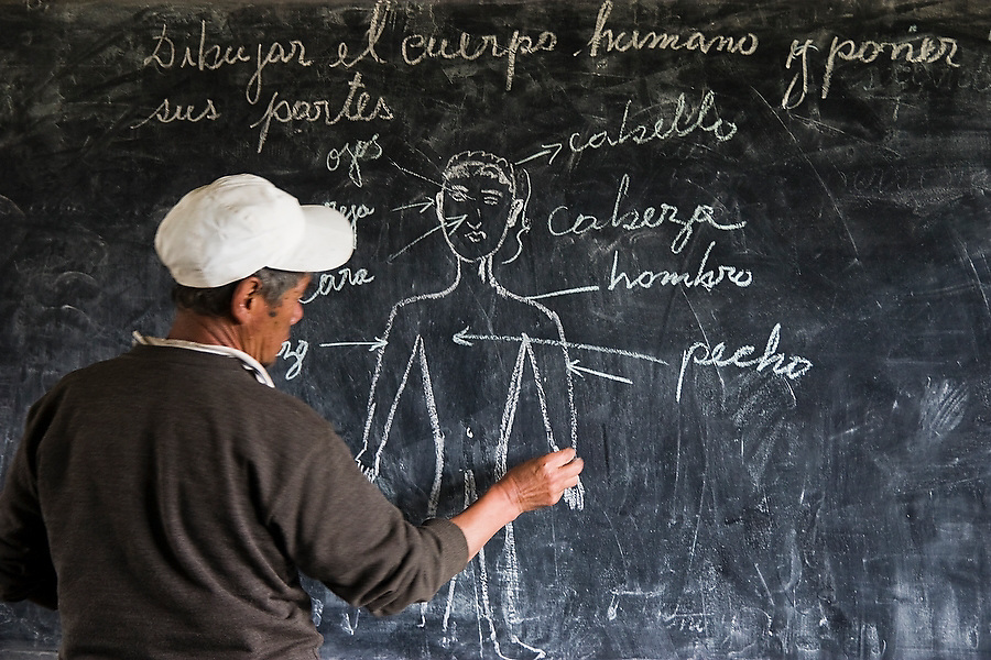 The teacher writes out a Spanish lesson on the blackboard in the small elementary school in Q'eros, Cordillera de Paucartambo, Andes Mountains, Peru on September 15, 2005. The students are taught in both their native Quechua and Spanish, the official language of Peru. The Q'eros, a Quecha people living in the Peruvian Andes, are considered the last direct descendants of the Incas and proudly maintain many of the ancient traditions.