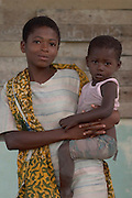 Teenage girl holding younger sister.