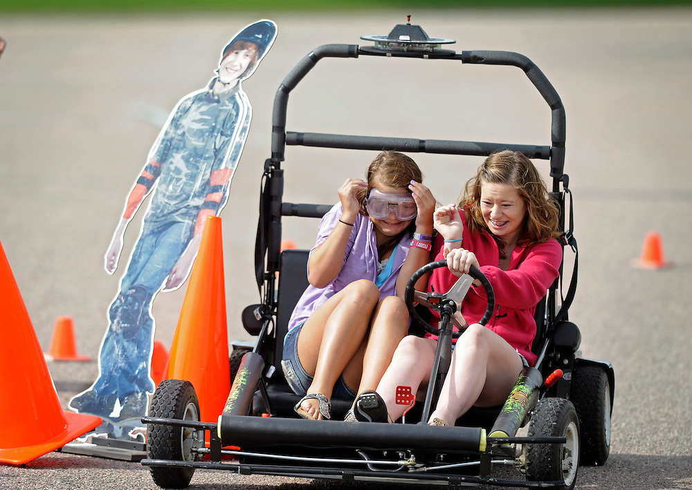 Elizabeth Jones, 14, (left) winces while wearing impaired goggles after Abby Bott, 15, ran into a skater cutout during drivers education class at Washington High School. The National Guard offered the simulated impaired driving experience (SIDNE), a remote control go kart, to educate students on the effects of driving under the influence.