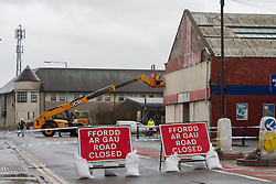 © Licensed to London News Pictures. 23/12/2013. Aberystwyth, UK.Workers race to patch up the disused Kwik Save building on Park Avenue in Aberystwyth after large panels were shaken loose by strong winds this morning (23/12/2013). Stormy seas at Aberystwyth this morning, 23rd December 2013. There are 127 flood alerts in place across the UK as stormy weather reaches the country. Photo credit : Jon Freeman/LNP