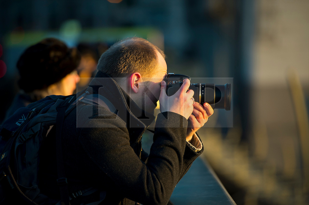 © Licensed to London News Pictures. 16/02/2016. London, UK. A man takes a picture as the sun rises  behind Tower Bridge in central London on a cold winter morning. Temperatures in the capital dropped below zero last night. Photo credit: Ben Cawthra/LNP
