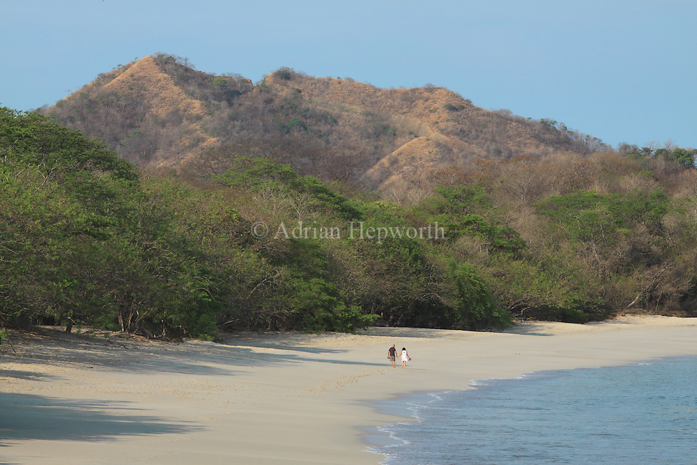 Tourists walking on Conchal Beach, Guanacaste, Costa Rica. <br /> <br /> For pricing click on ADD TO CART (above). We accept payments via PayPal.