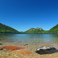 Picture perfect of Jordan Pond in the summer month of August. This waterscape is in the heart of Acadia National Park on Mount Desert Island and one of the best photo location for landscape photography. The shore line and rocks in the foreground provide interesting elements for a pleasing composition while the South and North Bubbles in the background are iconic photo subjects. Since the 1800's, people have come here for popovers and this picturesque view of the bubbles. <br /> The pond has clear water, with visibility normally 46 feet (14 m) and occasions of up to 60 feet (18 m) recorded, the deepest in Maine. It serves as the water supply for the village of Seal Harbor.<br /> <br /> Jordan Pond and the Bubbles landscape photography pictures are available as museum quality photography prints, canvas prints, acrylic prints, wood or metal prints. Prints may be framed and matted to the individual liking and room decor needs:<br /> <br /> http://juergen-roth.pixels.com/featured/jordan-pond-and-the-bubbles-juergen-roth.html<br /> <br /> Good light and happy photo making! <br /> <br /> My best, <br /> <br /> Juergen <br /> Image Licensing: http://www.RothGalleries.com <br /> Fine Art Prints: http://fineartamerica.com/profiles/juergen-roth.html <br /> Photo Blog: http://whereintheworldisjuergen.blogspot.com <br /> Twitter: https://twitter.com/naturefineart <br /> Facebook: https://www.facebook.com/naturefineart <br /> Instagram: https://www.instagram.com/rothgalleries