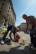 Race security touches-up some sketchy cobble sections 150 meters from the finish in front of Milan's Duomo.