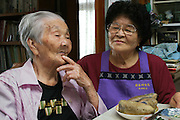 "(MODEL RELEASED IMAGE). Tama Matsuda, 100 years old, and her daughter-in-law Keiko, 75, with beni imo -purple Okinawan potatoes that they are eating for lunch. (Supporting image from the project Hungry Planet: What the World Eats) The Matsuda family is one of the thirty families featured in the book Hungry Planet: What the World Eats (p. 186). Hara hachi bu: ""eat only until 80 percent full,"" say older Okinawans. The island has been the focus in recent years of researchers trying to discover why a disproportionately large number of Okinawans are living to age 100 or more."