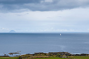 Single yacht in Scottish landscape with in the background Ailsa Craig island in the Firth of Clyde south of the Isle of Arran, Scotland