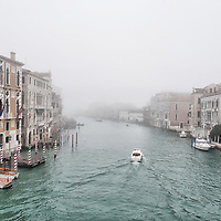 VENICE, ITALY - JANUARY 05: A gondolier sails under Rialto Bridge on an unusually empty Grand Canal as thick fog shrouds the city, on November 24, 2012 in Venice, Italy. Venice woke up this morning under a heavy blanket of fog adding to the atmosphere of the city.