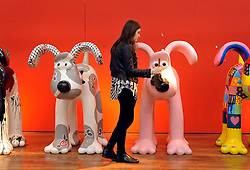 © Licensed to London News Pictures. 18/09/2013. Bristol, UK. Rowena Bown dusts off a Gromit at the Gromit Unleashed final exhibition to the public before the dogs are auctioned off next month to raise money for the Bristol Children's Hospital.  The exhibition shows all 80 Gromits and is in the former Habitat building next to the Royal West of England Academy on Queens Road. 18 September 2013.<br /> Photo credit : Simon Chapman/LNP