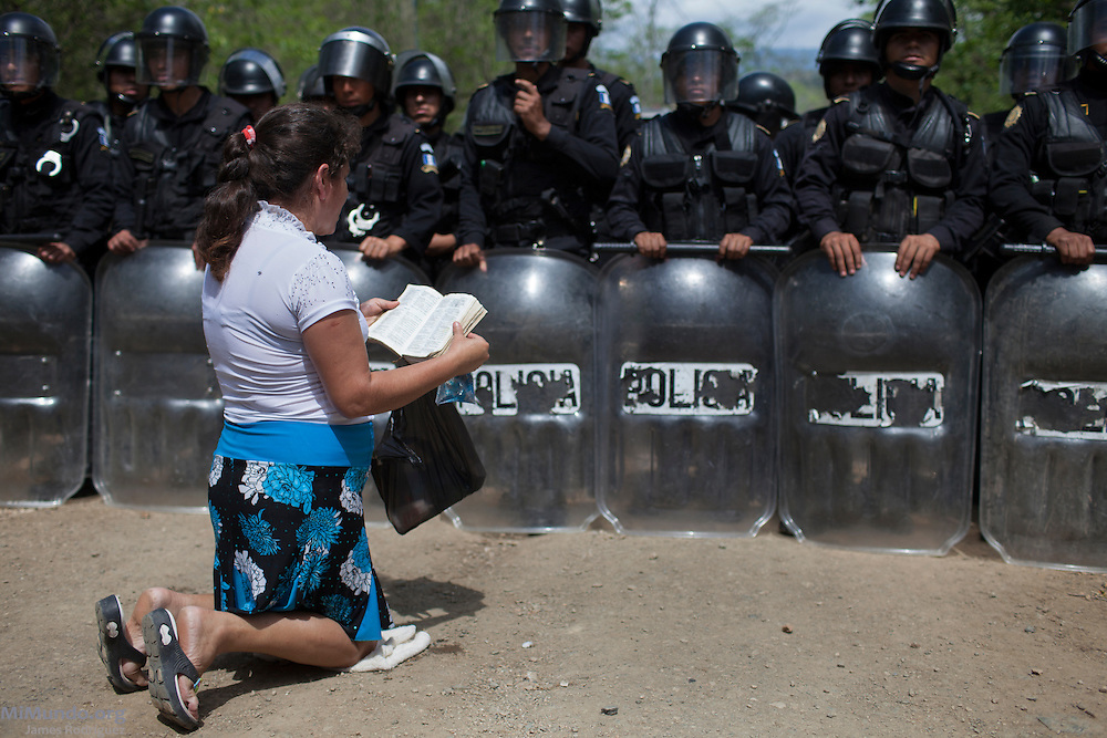 A local woman from the La Puya resistance prays and reads the bible as she attempts to dissuade the Police officers to retreat. After two years and two months of peacefully blocking the entrance to U.S.-based Kappes, Cassiday & Associates (KCA) El Tambor gold mine, local residents of San Jose del Golfo and San Pedro Ayampuc were violently evicted by Guatemalan Police forces in order to introduce heavy machinery inside the industrial site. La Puya, San Pedro Ayampuc, Guatemala. May 23, 2014.