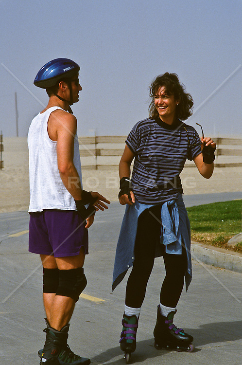 couple in Venice, CA on rollerblades stopping to talk