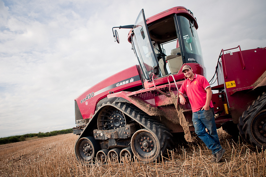 A smiling young farmer leaning against his red case 450 tractor in his field